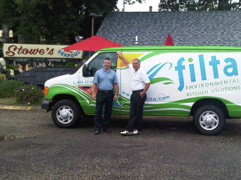Matt Neeley and Neil Groglio, co-owners of a Filta franchise in Shelton, in front of their first customer, Stowe's Seafood in Stratford. Photo: Contributed Photo / Connecticut Post Contributed