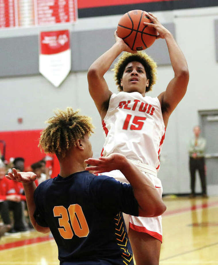 Alton's Dante' Herrin (15), shown shooting over O'Fallon's Dawson Algee in a Dec. 10 SWC game at Alton High in Godfrey, put up a double-double on Friday night in the Redbirds' win over Romeoville at the Centralia Tourney. Photo: Greg Shashack / The Telegraph