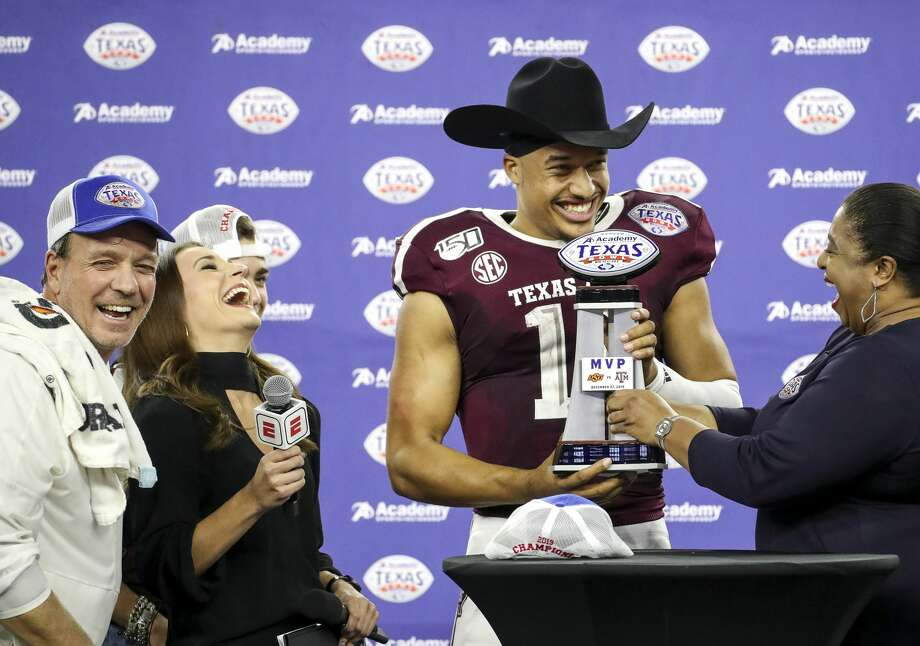 Texas A&M Aggies quarterback Kellen Mond (11) laughs with Texas A&M Aggies head coach Jimbo Fisher, left, as he is given the MVP trophy after the Texas A&M Aggies beat the Oklahoma State Cowboys in the Texas Bowl at NRG Stadium on Friday, Dec. 27, 2019, in Houston. Photo: Jon Shapley/Staff Photographer