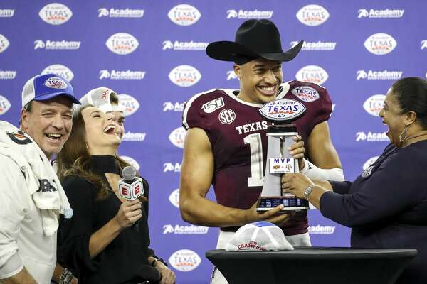 Texas A&M Aggies quarterback Kellen Mond (11) laughs with Texas A&M Aggies head coach Jimbo Fisher, left, as he is given the MVP trophy after the Texas A&M Aggies beat the Oklahoma State Cowboys in the Texas Bowl at NRG Stadium on Friday, Dec. 27, 2019, in Houston.