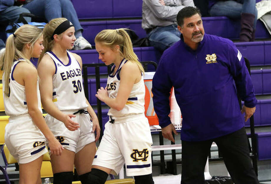 CM coach Jonathan Denney (right) delivers a final word to Tori Standefer, who joins teammates Jenna Christeson (30) and Kelbie Zupan (left) on the Eagles bench during a CM/Adidas Shootout game vs. O'Fallon on Dec. 20 in Bethalto. Denney picked up career win No. 300 on Friday night. Photo: Greg Shashack / The Telegraph
