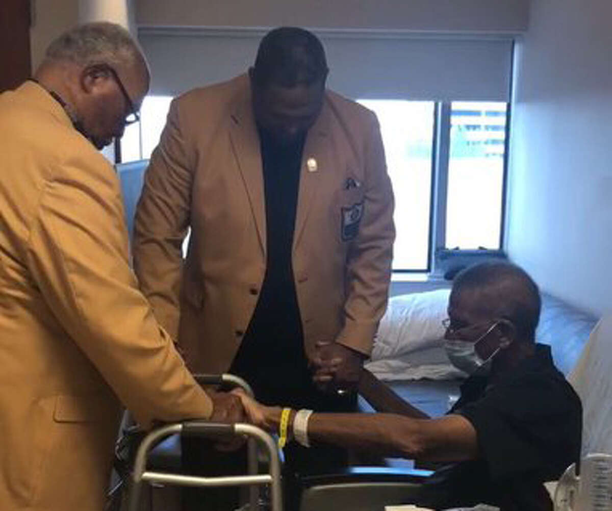 Hall of Famers Curley Culp, left, and Robert Brazile share a moment of prayer with Kenny Houston, right. Houston, regarded as the greatest strong safety in NFL history, is doing better in his weeks-long battle with leukemia.