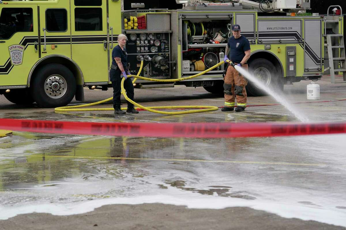 Members of the Houston Fire Dept. Little York Station wash blood from a parking lot Saturday, Dec. 28, 2019, in Houston in the 8500 block Sweetwater Lane where two people were shot and killed and at least seven others injured in a drive-by shooting while they were filming a music video Friday night.