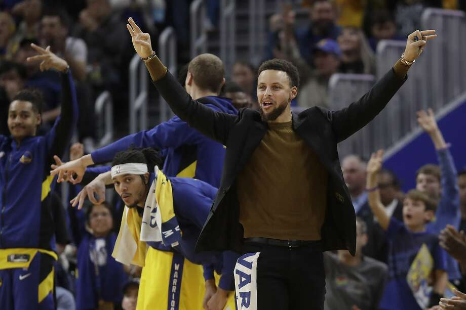 Injured Golden State Warriors guard Stephen Curry reacts after D'Angelo Russell scored a 3-pointer against the Phoenix Suns during the second half of an NBA basketball game in San Francisco, Friday, Dec. 27, 2019. (AP Photo/Jeff Chiu) Photo: Jeff Chiu / Associated Press