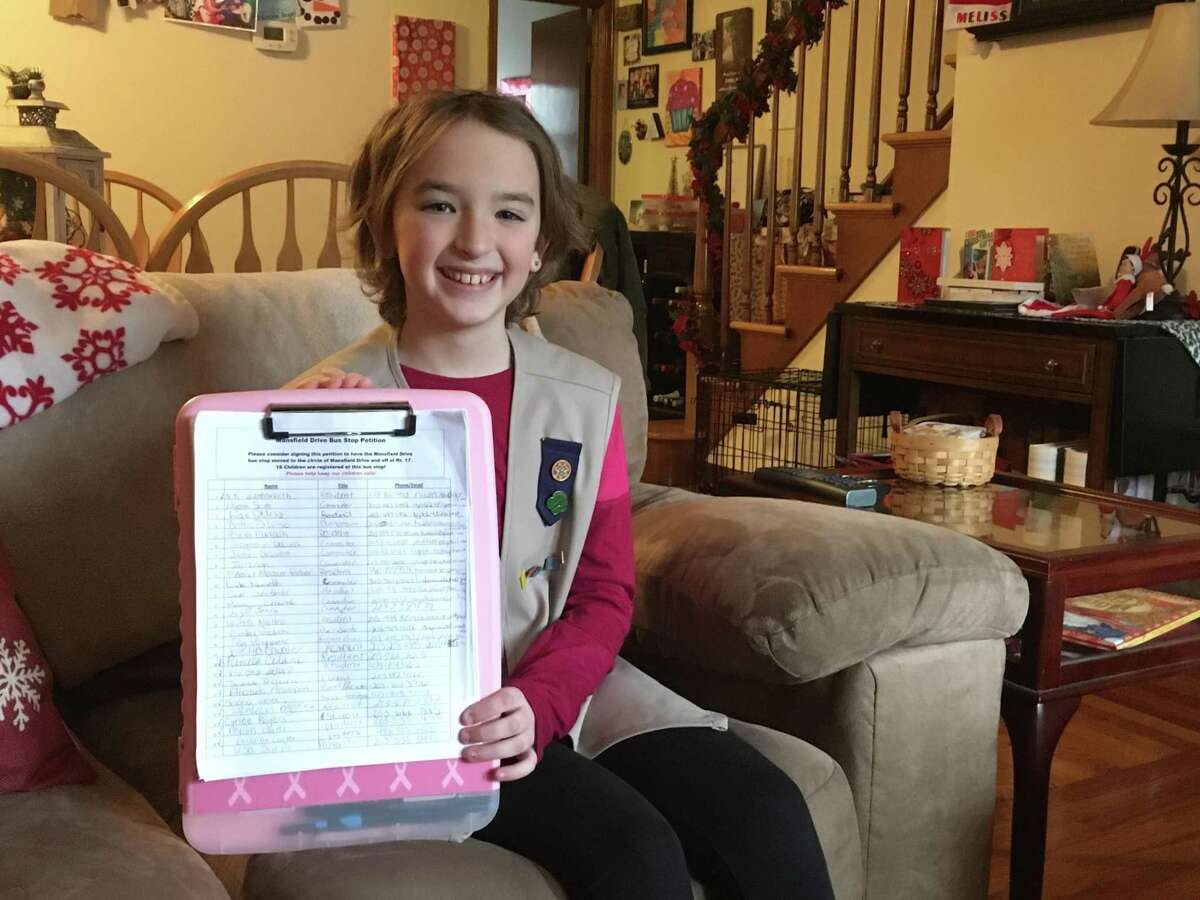 Kaylee Kowalewski, 11, shows off the signatures she's collected for a petition to have her bus stop moved, from the intersection of Route 17 and Mansfield Drive in North Branford to further along Mansfield Drive, which she says is a safer spot. A Girl Scout, she hopes to earn her Silver Award with the project. She is pictured in her home on Dec. 27, 2019.