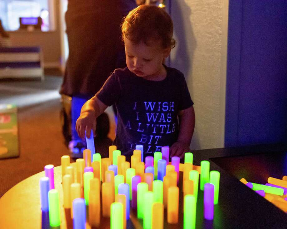 Eighteen-month-old Holden Baker plays with glowing pegs at The Beaumont Children's Museum's Glow Mania on Saturday, December 28, 2019 with a variety of glowing activities for children. Fran Ruchalski/The Enterprise Photo: Fran Ruchalski/The Enterprise / Fran Ruchalski / The Enterprise