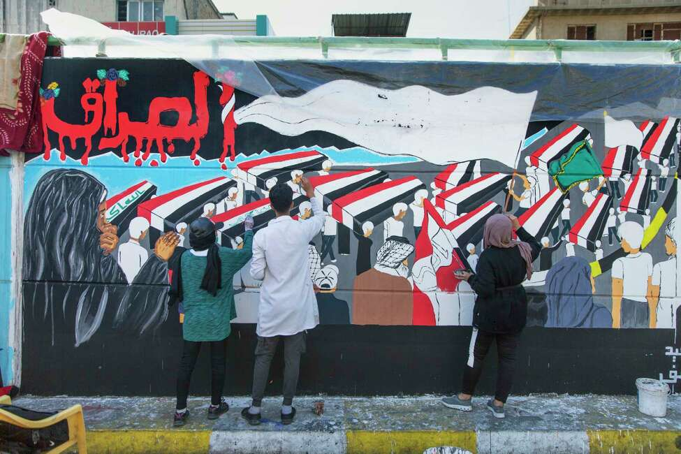 Anti-government activists work on a graffiti with Arabic that reads
