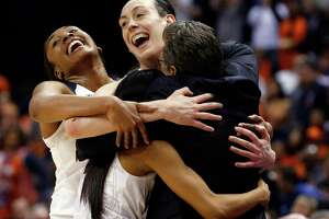 UConn's Morgan Tuck, left rear, Moriah Jefferson, front left, and Breanna Stewart hug coach Geno Auriemma, right, following the championship game against Syracuse in the women's Final Four in the NCAA college basketball tournament Tuesday, April 5, 2016, in Indianapolis. Connecticut won 82-51.