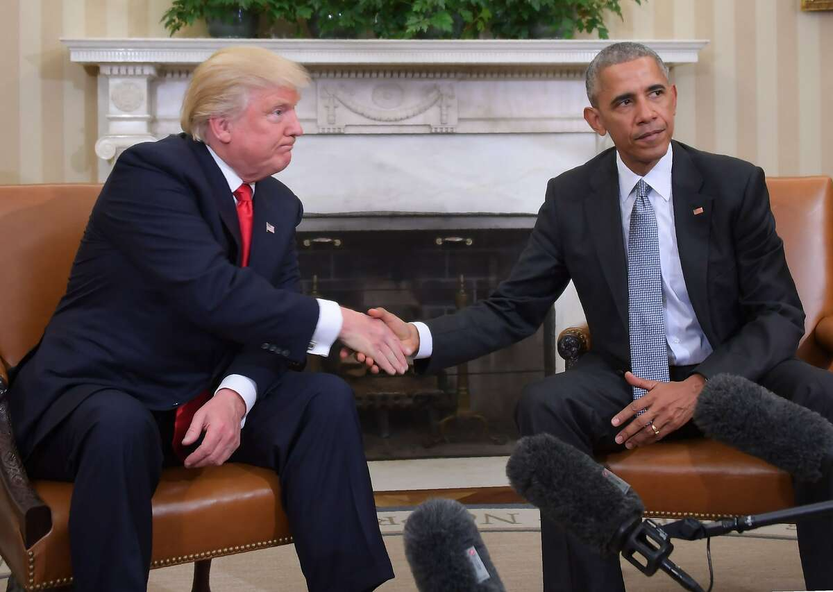 In this 2016 file photo President Barack Obama and President-elect Donald Trump shake hands during a transition planning meeting in the Oval Office at the White House in Washington, DC.