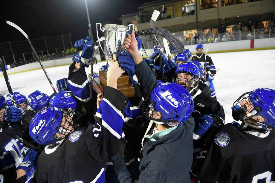 Darien players celebrate with the trophy after defeating Greenwich in the Winter Classic at the Greenwich Skating Club on Saturday. Photo: Matthew Brown / Hearst Connecticut Media / Stamford Advocate