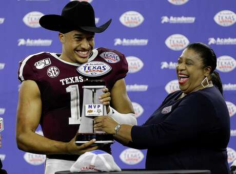 Texas A&M's Kellen Mond receives the MVP trophy after the Aggies defeated Oklahoma State 24-21 during the Texas Bowl at NRG Stadium on Friday night in Houston.