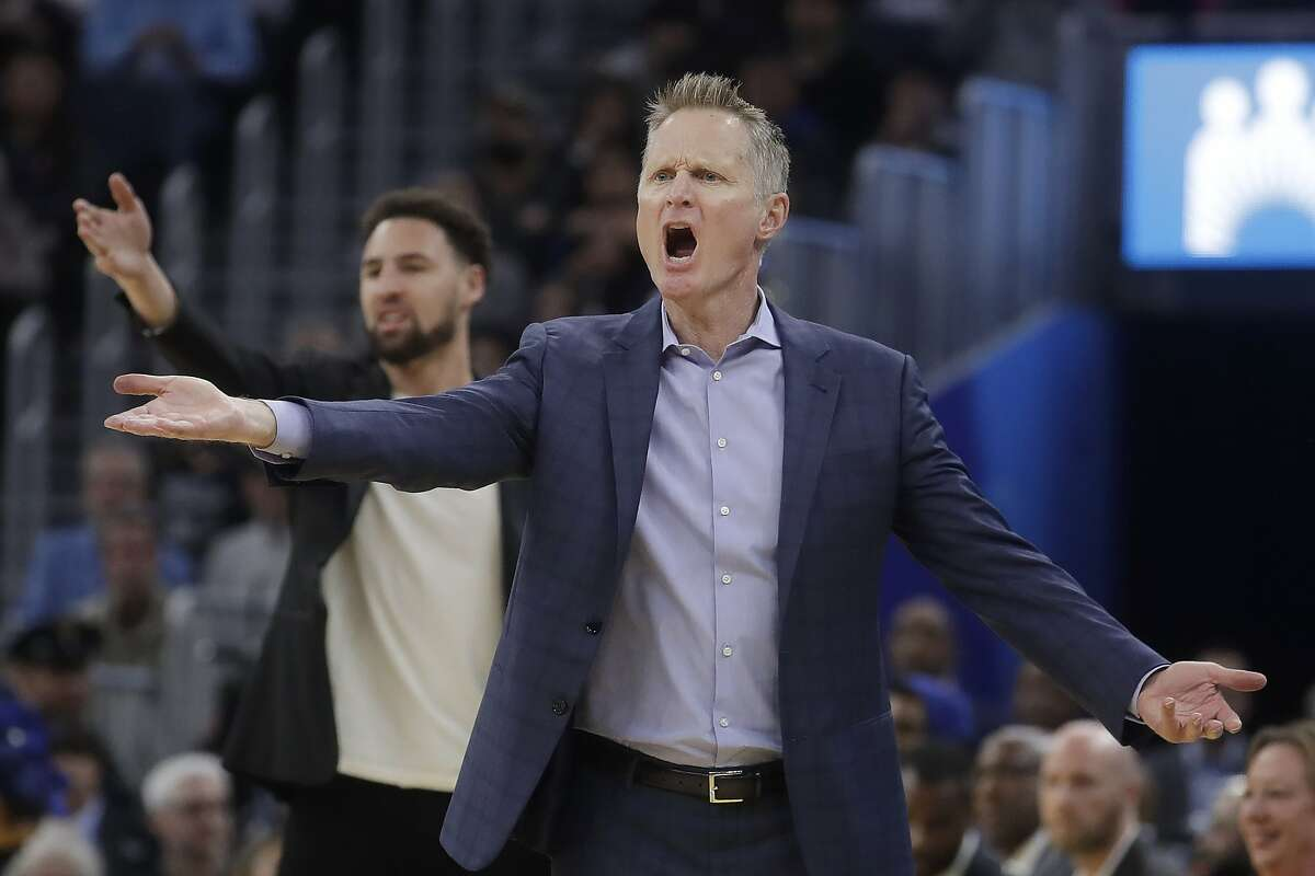 Golden State Warriors head coach Steve Kerr, foreground, and injured guard Klay Thompson react to an official's call during the first half of an NBA basketball game against the Dallas Mavericks in San Francisco, Saturday, Dec. 28, 2019. (AP Photo/Jeff Chiu)