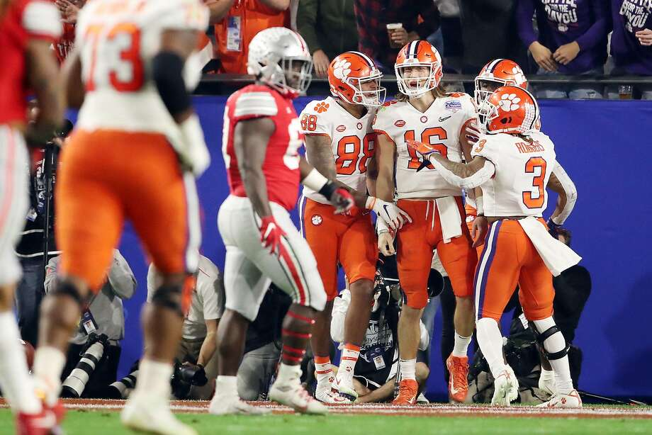 Clemson quarterback Trevor Lawrence (16) is congratulated by teammates after his 67-yard touchdown run late in the first half. Photo: Christian Petersen / Getty Images