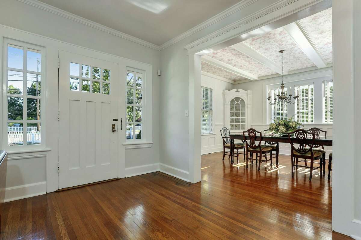 From the foyer there is a wide entrance into the formal dining room, which has a coffered ceiling, two built-in corner china cabinets, and wainscoting on the lower walls.
