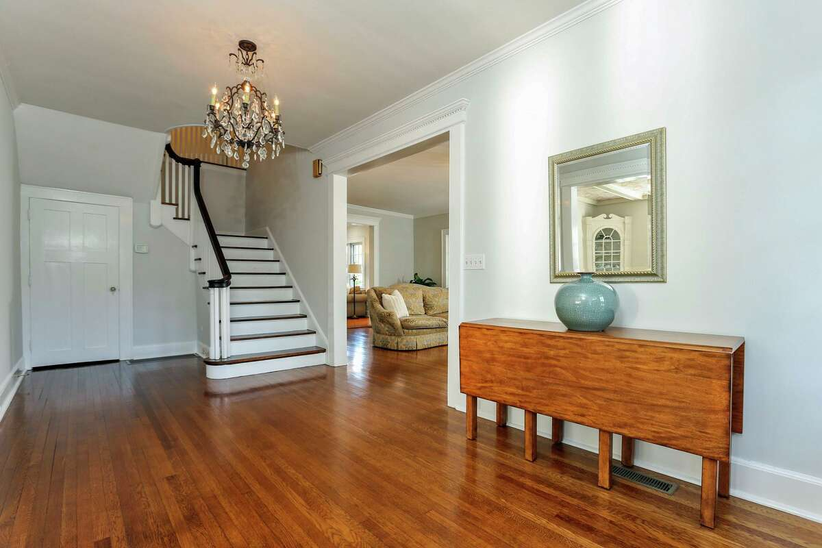 The center hall foyer provides access to the formal living and dining rooms and also has a powder room with a fabric ceiling.