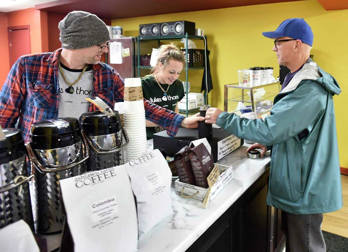 Faithful customer Mike Jones of Clinton visits Jules Calini Smith and her husband Thom Smith, owners of Jules & Thom coffe shop in Clinton, for a coffee refill on Dec. 10. The couple's shop offers their own unique speciality coffee drinks, artwork and a record music player playing vinyl disc albums.