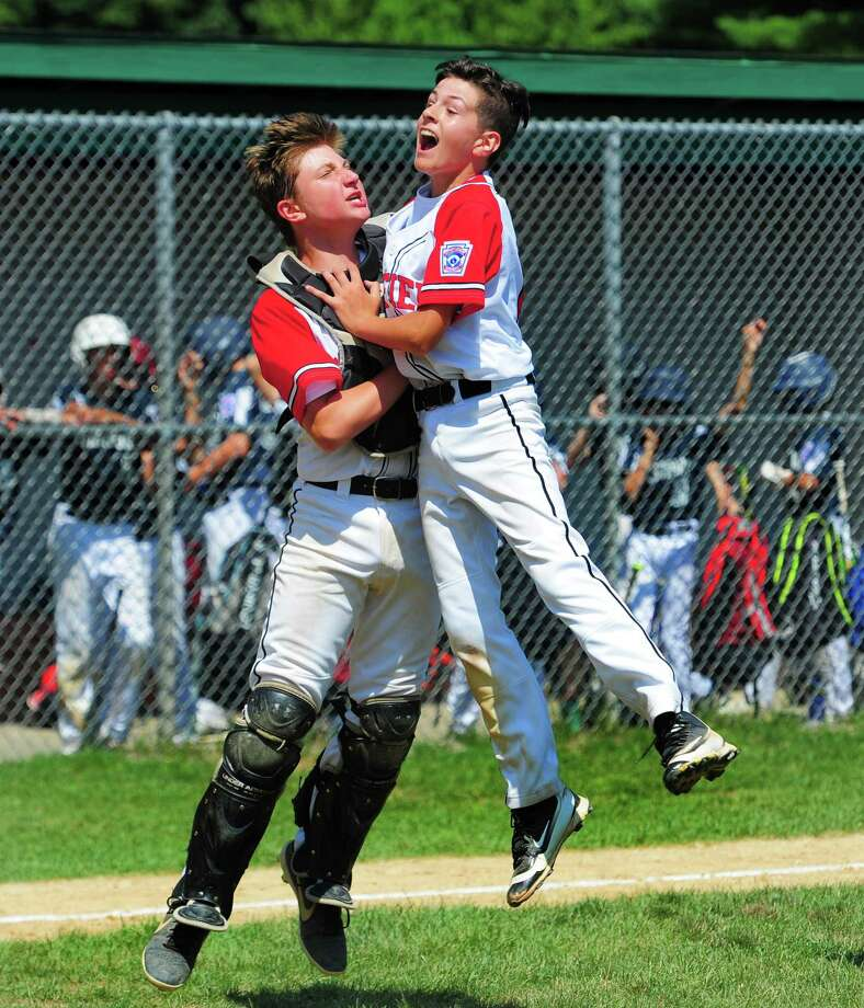 Fairfield American catcher Cooper Seek, left, and pitcher Kieran Scruggs celebrate the their win over Westport during District 2 little league baseball championship action at Unity Field in Trumbull, Conn., on Saturday July 13, 2019. Photo: Christian Abraham / Hearst Connecticut Media / Connecticut Post