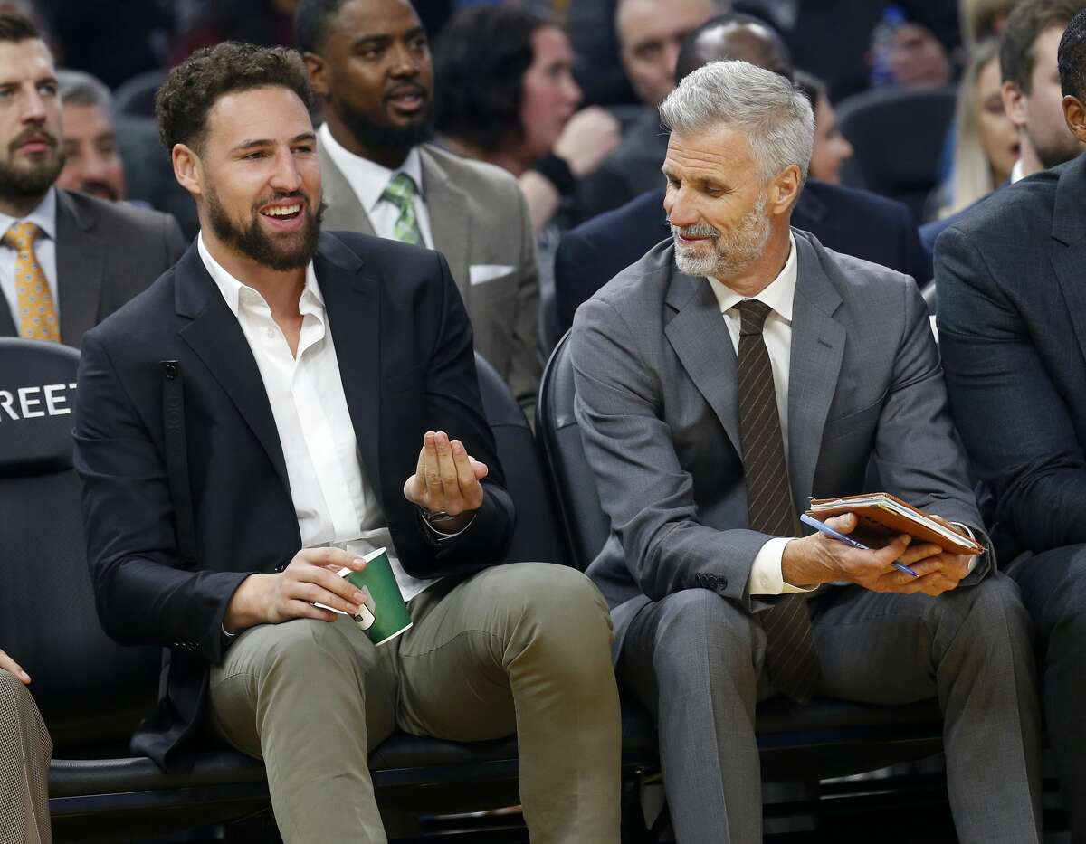 Golden State Warriors' Klay Thompson sits on the bench with assistant coach Bruce Fraser in the first quarter at the Chase Center on Monday, Nov. 25, 2019.