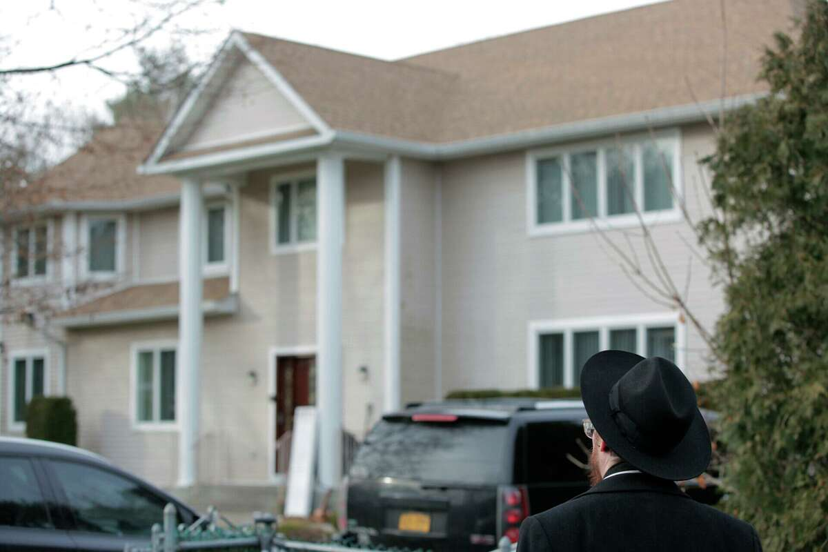 An onlooker stands outside a rabbi's residence in Monsey, N.Y., Sunday, Dec. 29, 2019, following a stabbing Saturday night during a Hanukkah celebration. (AP Photo/Julius Constantine Motal)