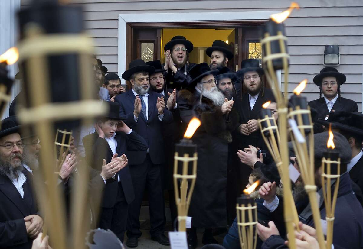 Community members celebrate the arrival of a new Torah at Chaim Rottenberg residence, Sunday, Dec. 29, 2019, in Monsey, N.Y. A day earlier, a knife-wielding man stormed into the home and stabbed multiple people as they celebrated Hanukkah in the Orthodox Jewish community. (AP Photo/Craig Ruttle)