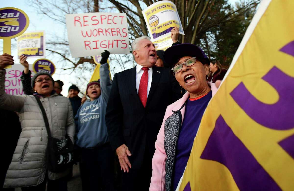 Fired worker Lucia Herrera join members of the 32BJ SEIU as they gather with Norwalk Mayor Harry Rilling to ask new owners of 40 Richards Avenue to re-hire sveral workers Tuesday, November 26, 2019, outside the building in Norwalk, Conn. Dozens of janitors, community activists and union members and supporters protested outside 40 Richards Ave. to demand that the building's new owners reinstate five office cleaners who lost the jobs on Halloween.
