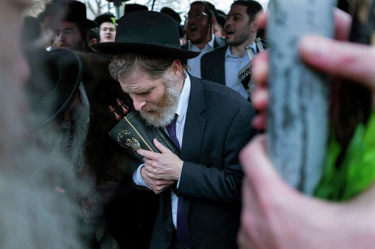 Community members celebrate the arrival of a new Torah near the rabbi's residence, Sunday, Dec. 29, 2019, in Monsey, N.Y. A day earlier, a knife-wielding man stormed into the home and stabbed multiple people as they celebrated Hanukkah in the Orthodox Jewish community.