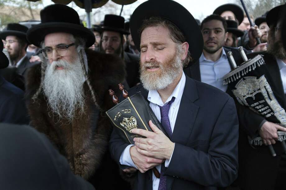 Community members, including Rabbi Chaim Rottenberg, left, celebrate the arrival of a new Torah near the rabbi's residence in Monsey, N.Y. A day earlier, a knife-wielding man stormed into the home and stabbed multiple people as they celebrated Hanukkah in the Orthodox Jewish community. (AP Photo/Craig Ruttle) Photo: Craig Ruttle, Associated Press