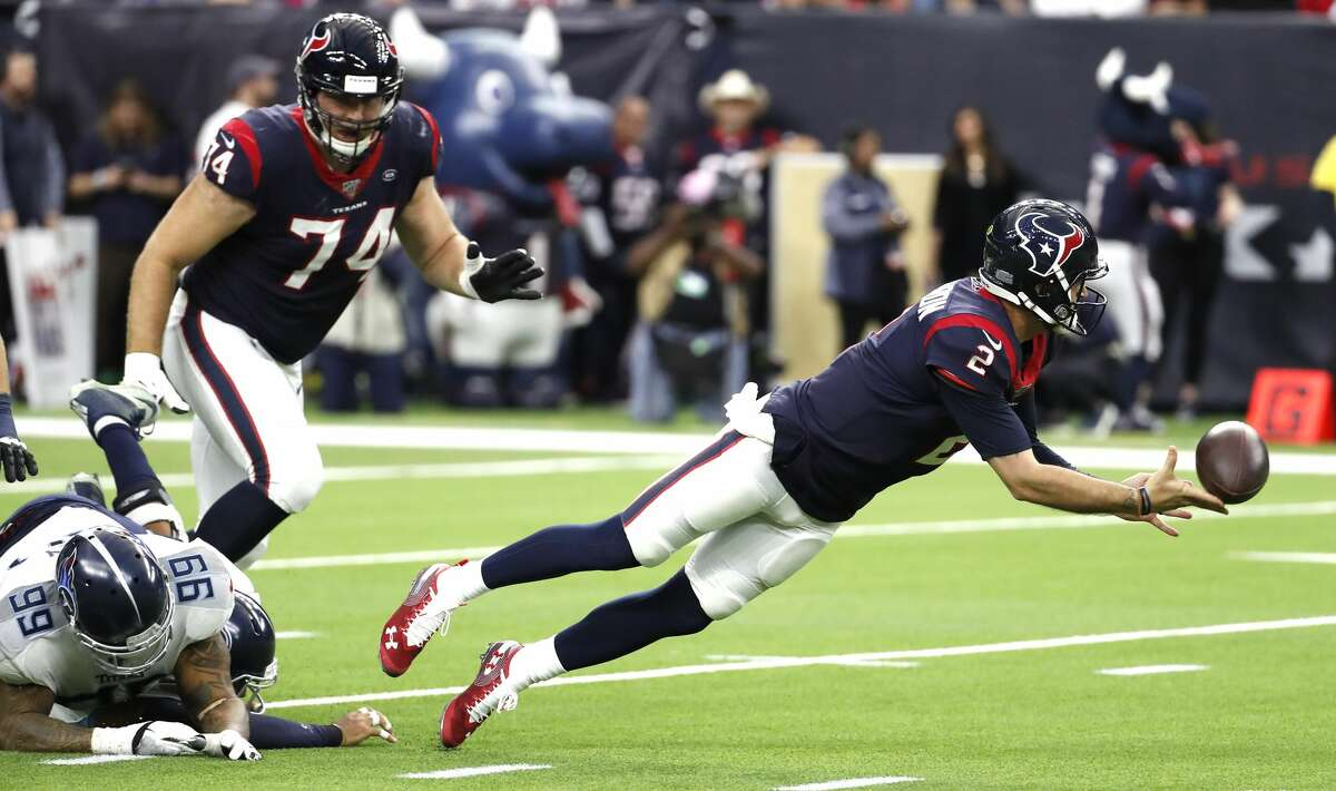 Texans quarterback AJ McCarron (2) dives away from the grasp of Titans defensive tackle Jurrell Casey (99) to complete a pass to running back Duke Johnson (25) for a first down during the second quarter Sunday.