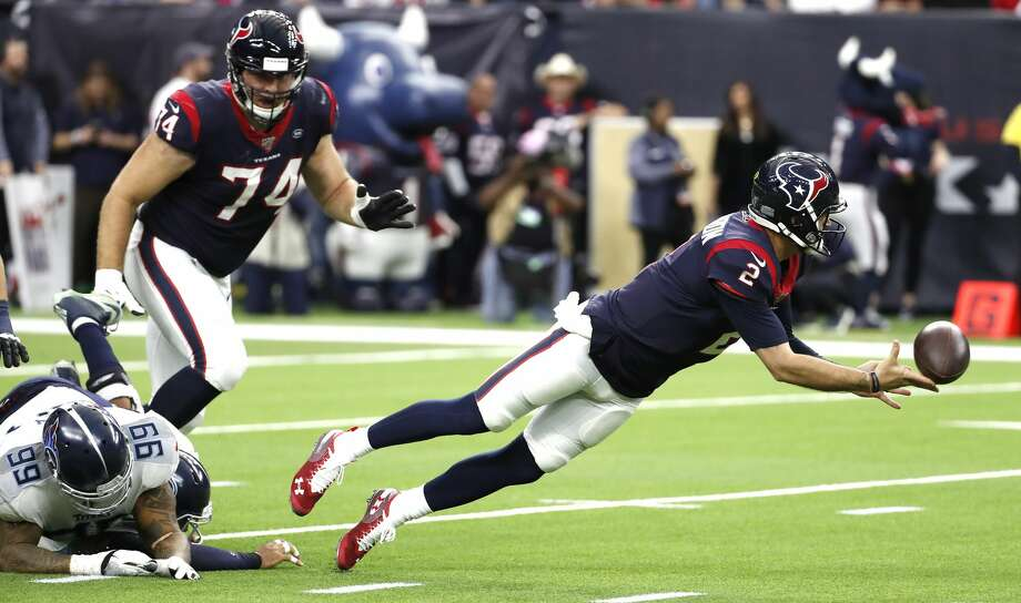 Texans quarterback AJ McCarron (2) dives away from the grasp of Titans defensive tackle Jurrell Casey (99) to complete a pass to running back Duke Johnson (25) for a first down during the second quarter Sunday. Photo: Brett Coomer/Staff Photographer