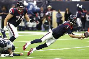 Houston Texans quarterback AJ McCarron (2) dive away from the grasp of Tennessee Titans defensive end Jurrell Casey (99) to complete a pass to running back Duke Johnson (25) for a first down during the second quarter of an NFL football game at NRG Stadium on Sunday, Dec. 29, 2019, in Houston.