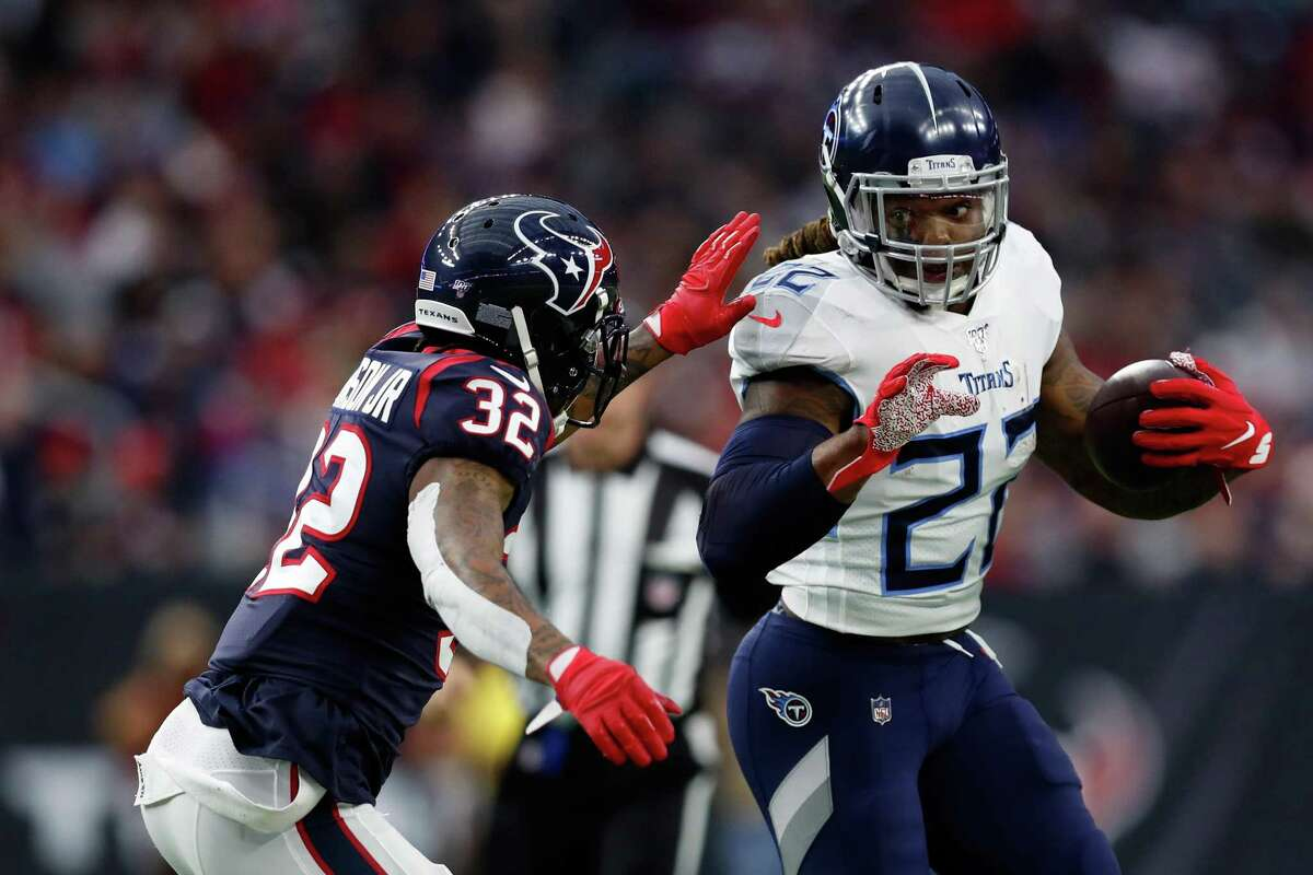 Derrick Henry (22) of the Tennessee Titans is pursued by Lonnie Johnson (32) of the Houston Texans during the first half at NRG Stadium on December 29, 2019 in Houston.