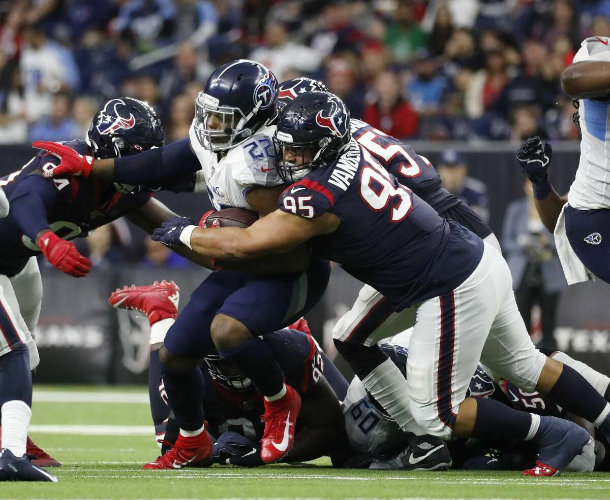 Tennessee Titans running back Derrick Henry (22) gets slowed down by Houston Texans defensive tackle Eddie Vanderdoes (95) during the second half of an NFL football game at NRG Stadium, Sunday, Dec. 29, 2019, in Houston.