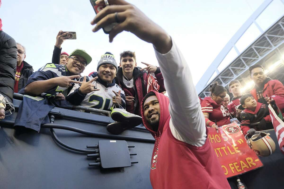 San Francisco 49ers' DeForest Buckner takes photos with fans before an NFL football game against the Seattle Seahawks, Sunday, Dec. 29, 2019, in Seattle. (AP Photo/Stephen Brashear)