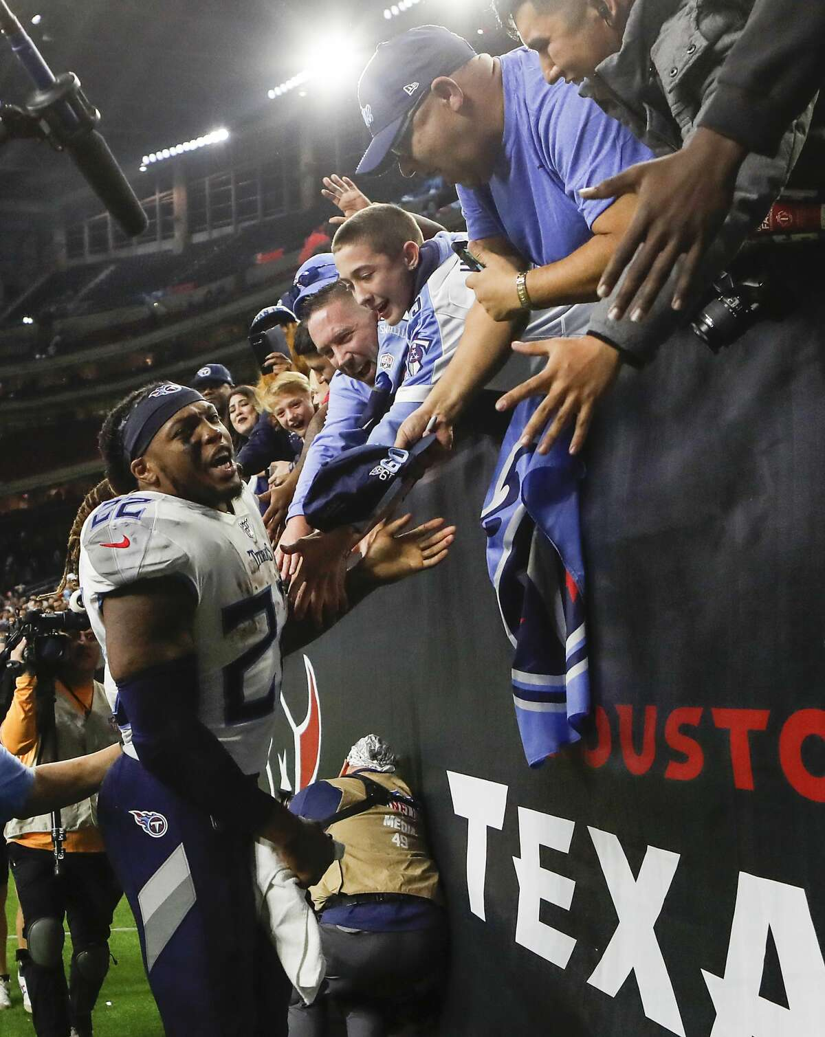 Tennessee Titans running back Derrick Henry (22) celebrates with Titans fans after beating the Houston Texans 35-14 in an NFL football game at NRG Stadium on Sunday, Dec. 29, 2019, in Houston.