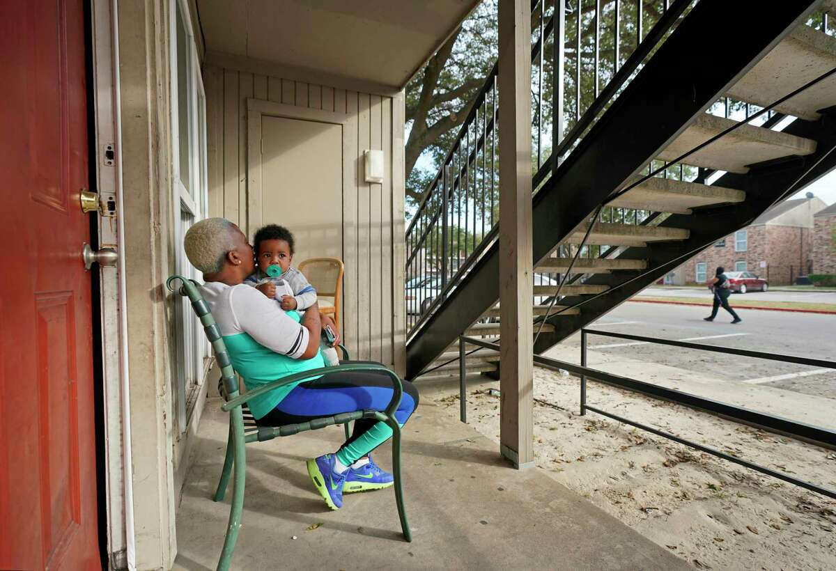 Shaunta Smith kisses her 7-month-old grandson, Trevion Easter, Jr., as she sits outside her apartment at Haverstock Hills, 5619 Aldine Bender Rd., Thursday, Dec. 5, 2019, in Houston. Prairie View A&M University is partnering with Haverstock Hills, a low-income apartment complex that has been notorious for crime and drugs, in hopes of creating a pathway to college for youth. The university will offer a range of services to the community, much of which will be directed toward students and juveniles, including college prep programs, family empowerment programs and support groups for parents, health awareness and services that address juvenile delinquency.