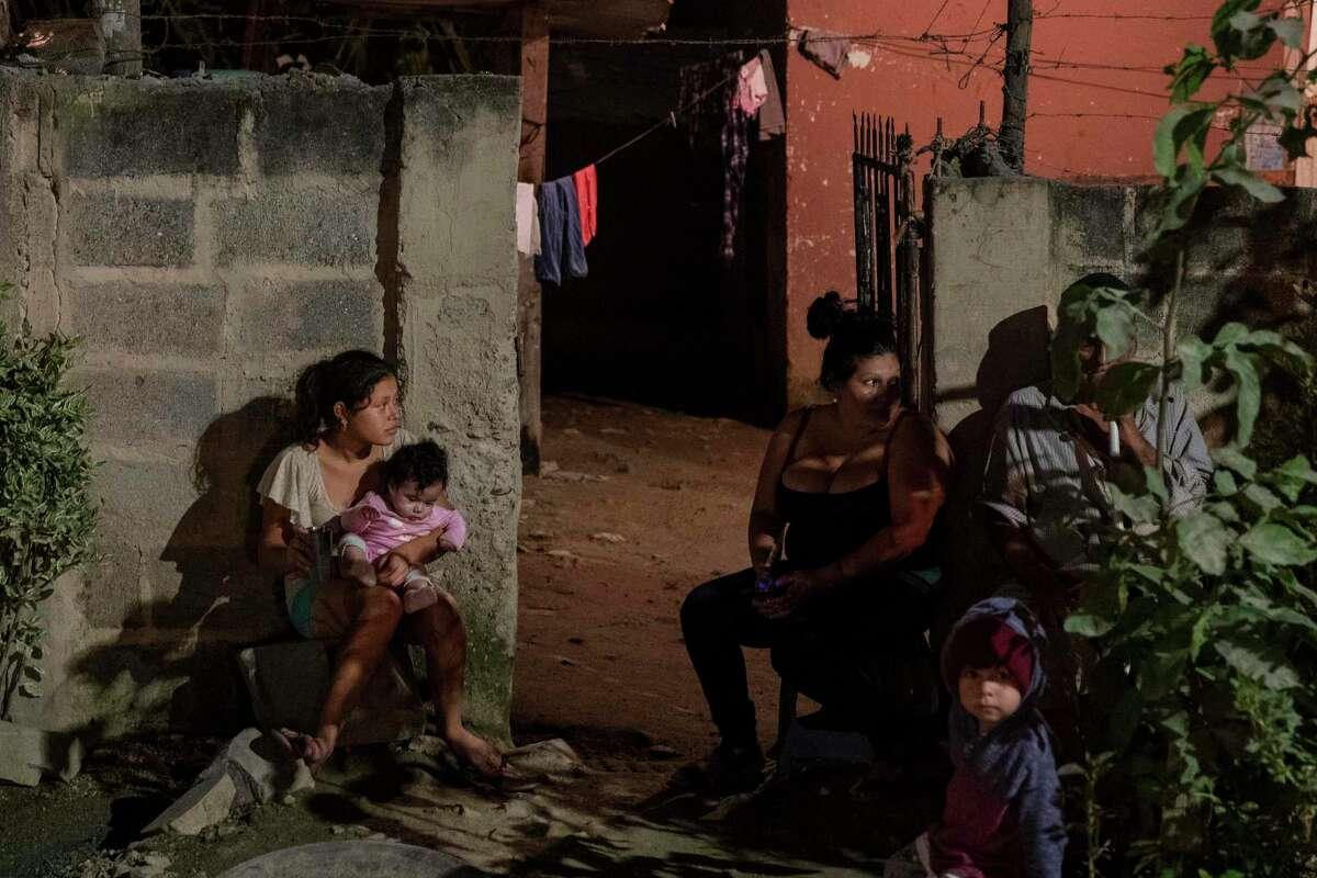 Una familia permanece sentada en el exterior de su casa mientras trabajadores del servicio forense investigan un cuerpo en el lugar de un crimen en el barrio Rivera Hernández de San Pedro Sula, Honduras, el 30 de noviembre de 2019.