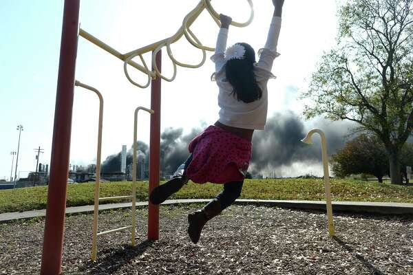 Jullissa Puente watches the thick smoke and flames that continued to erupt from the TPC plant as she plays at a nearby park with sister Adanli. Their father Abraham says the Beaumont family came down to Port Neches to pay their rent and stopped at the park to take photographs of the ongoing fire. Photo taken Wednesday, November 27, 2019 Kim Brent/The Enterprise