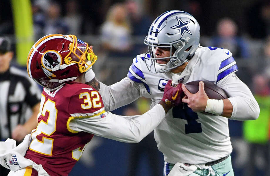 Dallas Cowboys quarterback Dak Prescott pushes Washington Redskins cornerback Jimmy Moreland to the ground on Sunday, Dec. 29, 2019. Photo: Washington Post Photo By Jonathan Newton / The Washington Post