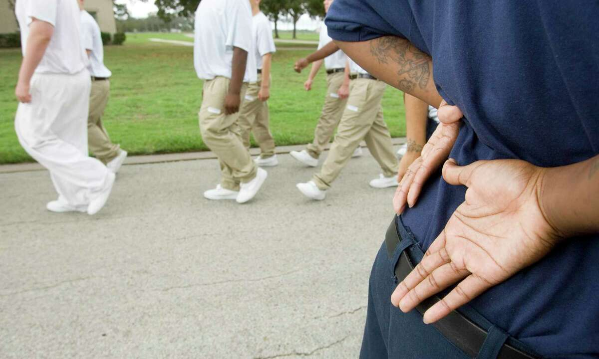 A youth at the Giddings State School holds his hands behind his back as he stands on the grounds while other students march to their next activity Thursday, Oct. 12, 2006. The agency has since changed names and closed some facilities, but Giddings still holds juvenile inmates. (Photo by Brett Coomer / Houston Chronicle) Contact: Tim Savoy (512) 351-0952