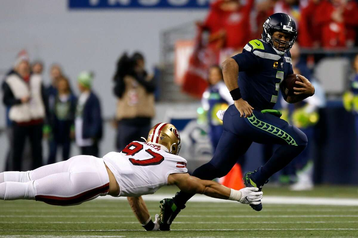 SEATTLE, WASHINGTON - DECEMBER 29: Defensive end Nick Bosa #97 of the San Francisco 49ers dives to tackle quarterback Russell Wilson #3 of the Seattle Seahawks during the game at CenturyLink Field on December 29, 2019 in Seattle, Washington. (Photo by Otto Greule Jr/Getty Images)