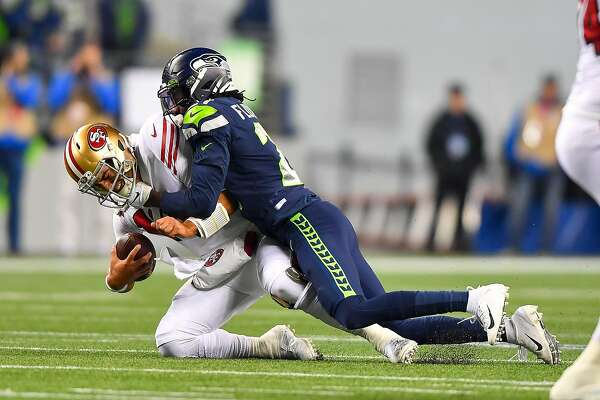 SEATTLE, WASHINGTON - DECEMBER 29: Tre Flowers #21 of the Seattle Seahawks sacks Jimmy Garoppolo #10 of the San Francisco 49ers during the first quarter of the game at CenturyLink Field on December 29, 2019 in Seattle, Washington. (Photo by Alika Jenner/Getty Images)