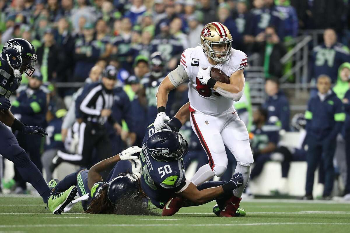 Tight end George Kittle #85 of the San Francisco 49ers runs against outside linebacker K.J. Wright #50 of the Seattle Seahawks during the game at CenturyLink Field on December 29, 2019 in Seattle, Washington.