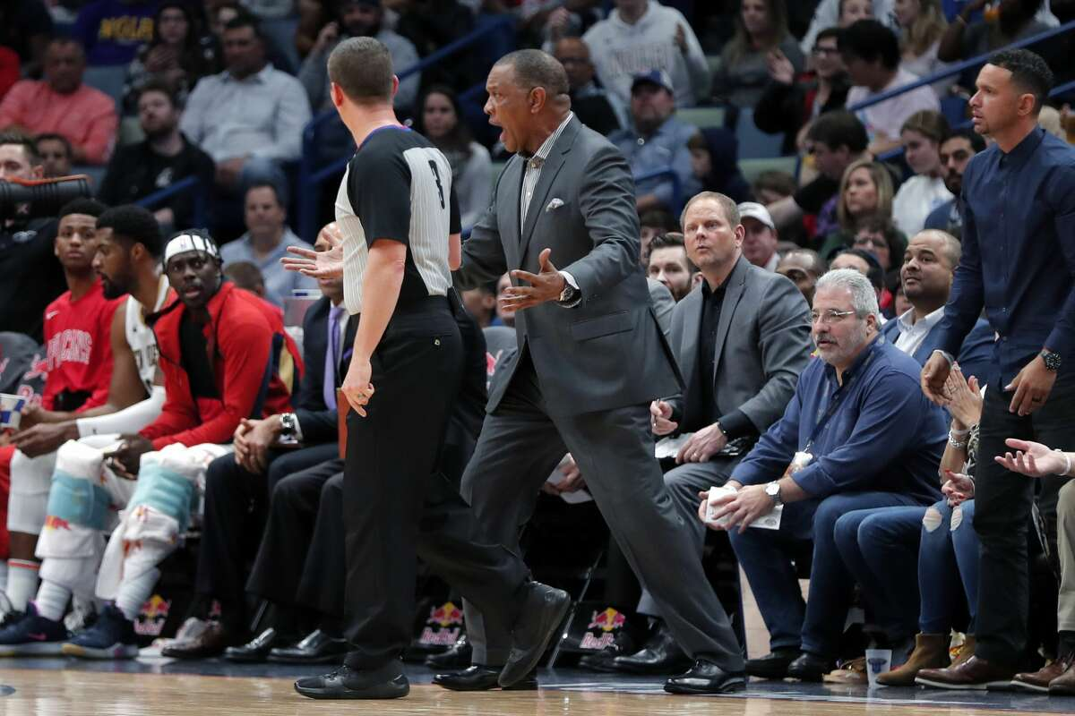 New Orleans Pelicans head coach Alvin Gentry, center right, challenges referee Nick Buchert in the first half of an NBA basketball game against the Houston Rockets in New Orleans, Sunday, Dec. 29, 2019. (AP Photo/Gerald Herbert)