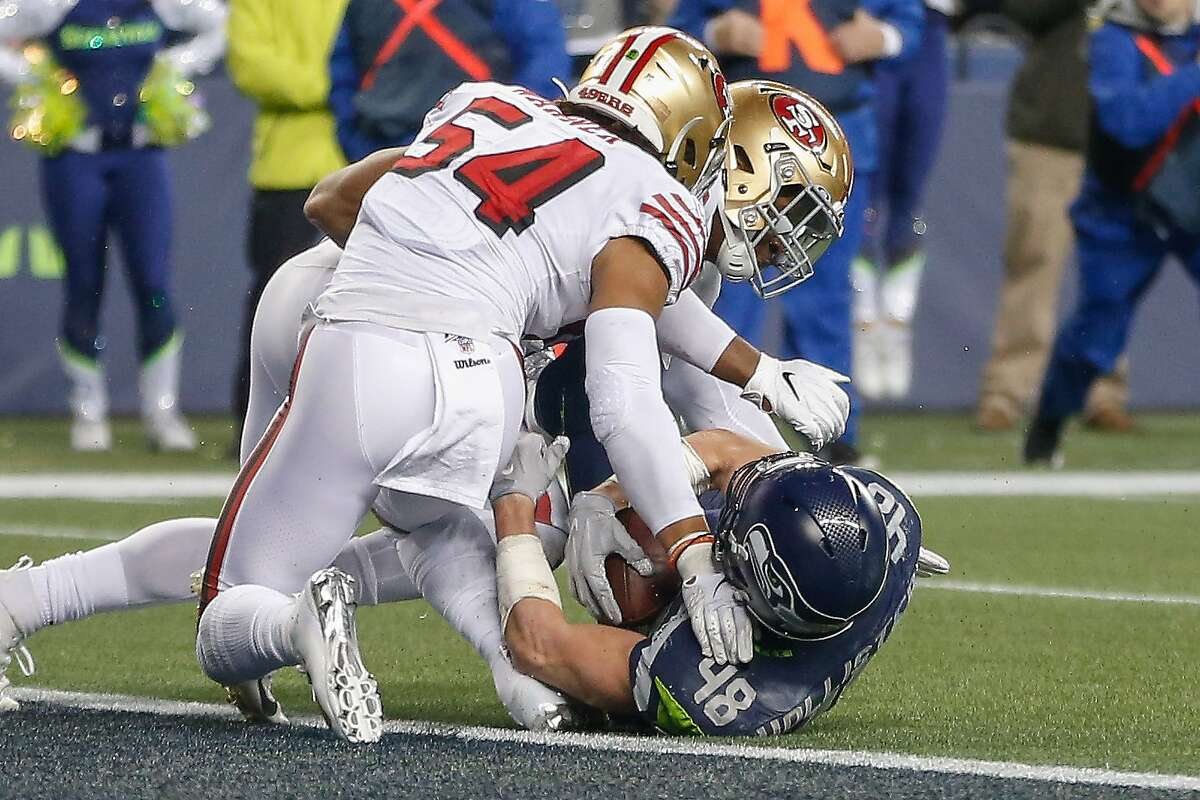 Tight end Jacob Hollister #48 of the Seattle Seahawks is stopped just short of the goal line by linebacker Dre Greenlaw #57 and linebacker Fred Warner #54 of the San Francisco 49ers in the fourth quarter at CenturyLink Field on December 29, 2019 in Seattle, Washington. (Photo by Otto Greule Jr/Getty Images)