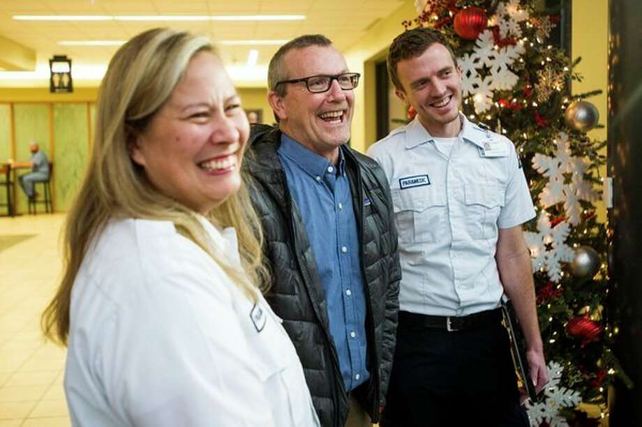 Mike O'Keefe, center, laughs with MidMichigan Medical Center-Midland paramedics Jungja McCoy, left, and Cody Pedlar, right, who transported O'Keefe to the hospital on Oct. 12 after he had a heart attack while chopping wood outside of his home, during a celebration Tuesday, Dec. 24, 2019 at the hospital. (Katy Kildee/kkildee@mdn.net)