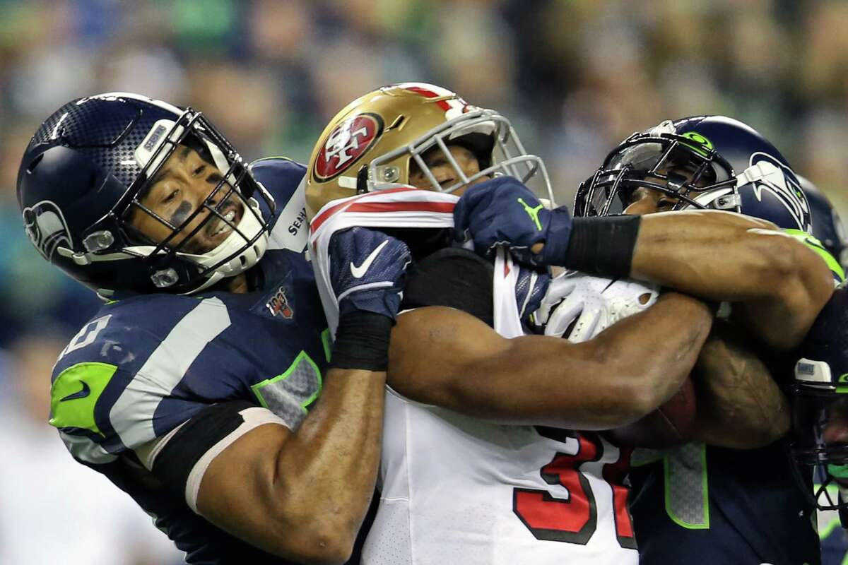 Seattle Seahawks outside linebacker K.J. Wright (50) and linebacker Bobby Wagner (54) stop San Francisco 49ers running back Raheem Mostert (31) in the first half of Seattle's game against San Francisco, Sunday, Dec. 29, 2019 at CenturyLink Field.