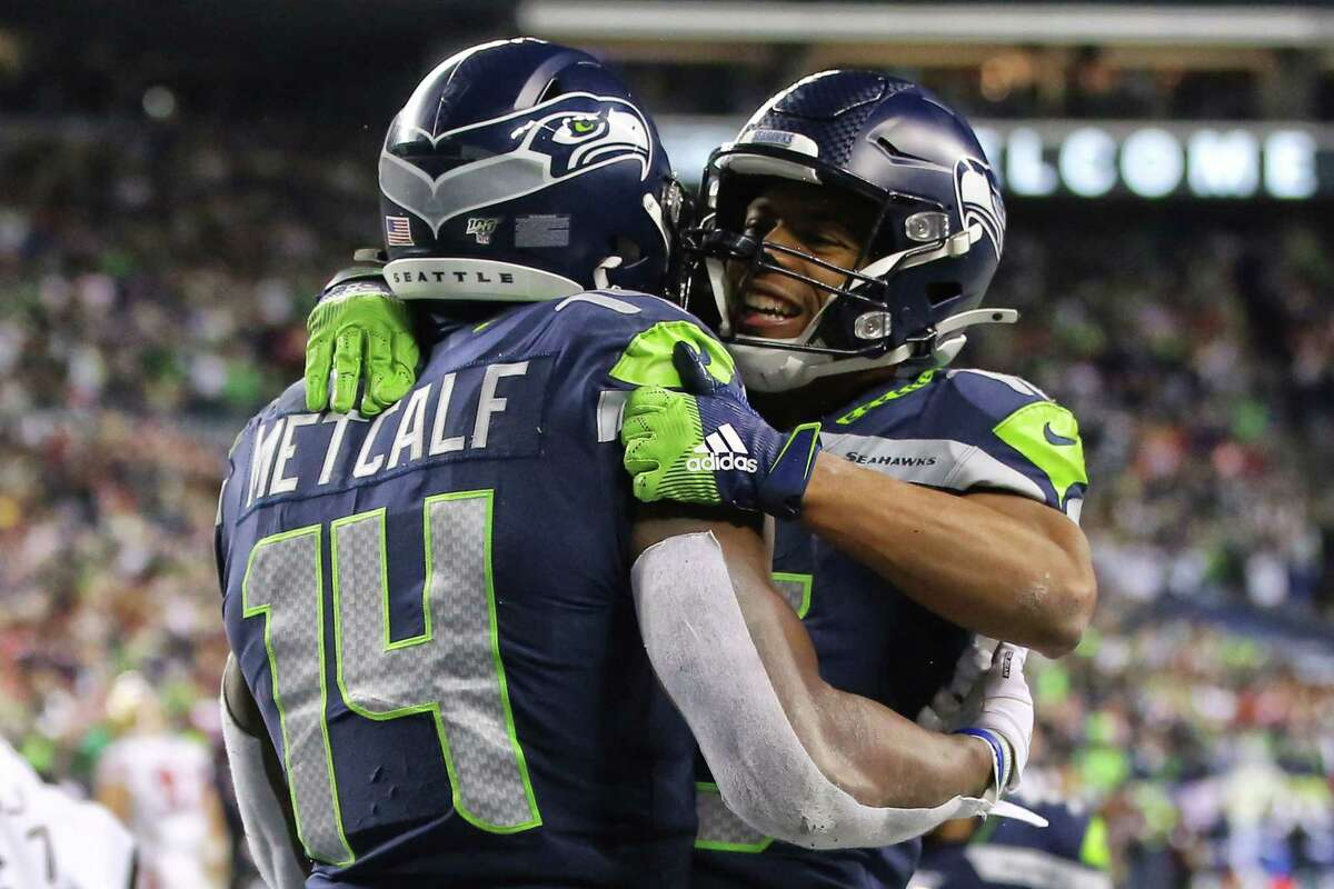 Tyler Lockett hugs Seattle Seahawks wide receiver D.K. Metcalf (14) after Metcalf scored a 14-yard touchdown in the fourth quarter of Seattle's game against San Francisco, Sunday, Dec. 29, 2019 at CenturyLink Field.