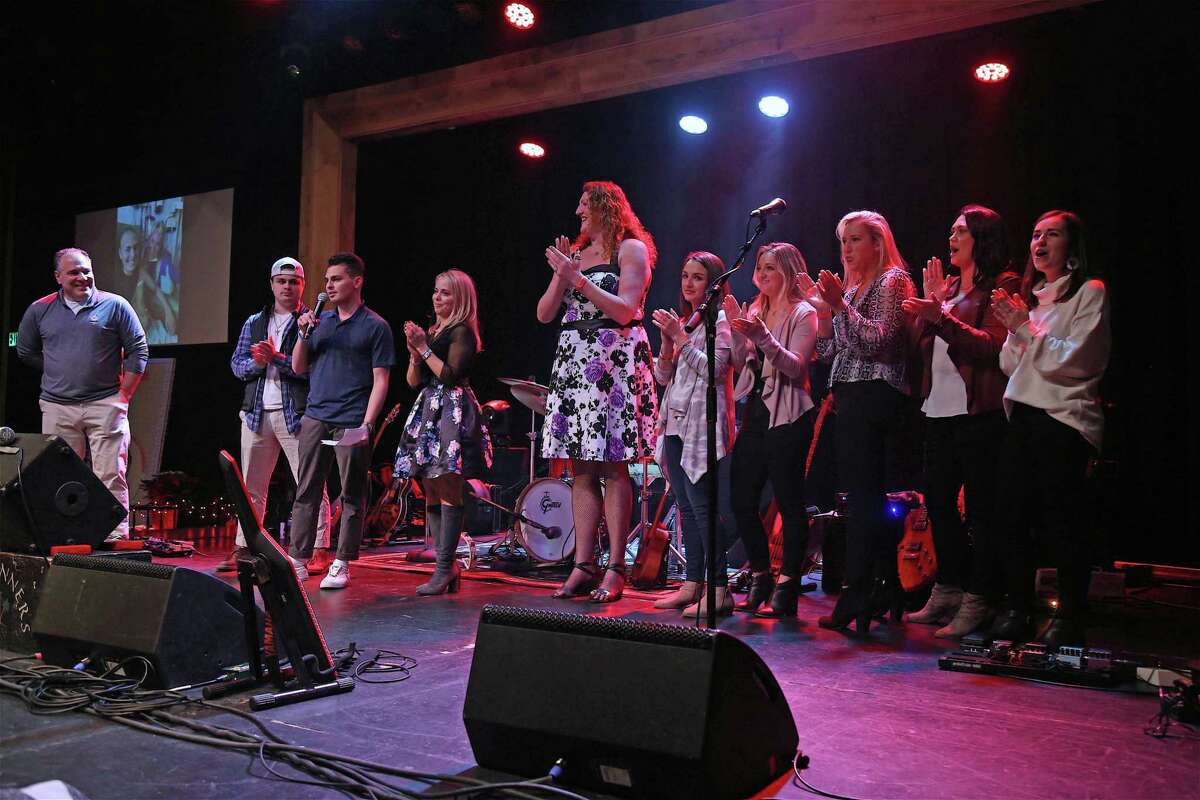 The Capalbo family joins staff members of the Boston Children's Hospital on stage at the Capalbo Strong Crushed Cancer Event at the Fairfield Theatre Company on Sunday, Dec. 29, 2019, in Fairfield, Conn.