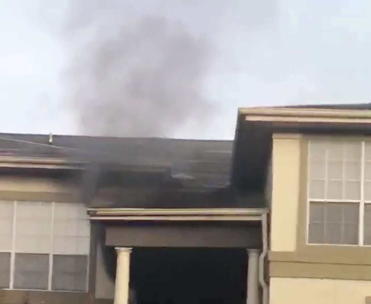 Smoke pours out of an apartment in the 9700 block of Cypresswood Drive on Monday, Dec. 30, 2019.