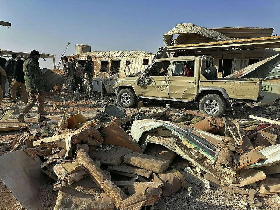 """Fighters from the Kataeb Hezbollah, or Hezbollah Brigades militia, inspect the destruction at their headquarters in the aftermath of a U.S. airstrike in Qaim, Iraq, Monday, Dec. 30, 2019. The Iranian-backed militia said Monday that the death toll from U.S. military strikes in Iraq and Syria against its fighters has risen to 25, vowing to exact revenge for the """"aggression of evil American ravens."""" (AP Photo) Photo: Associated Press"""